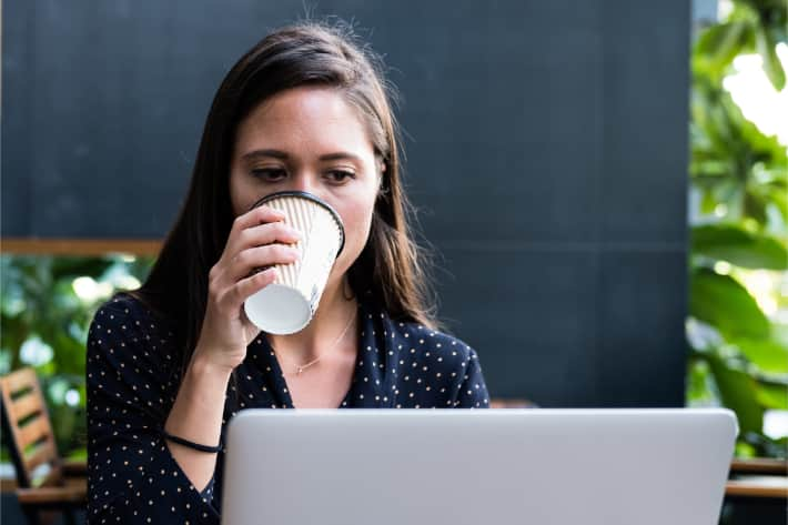 Woman browsing on laptop and sipping coffee